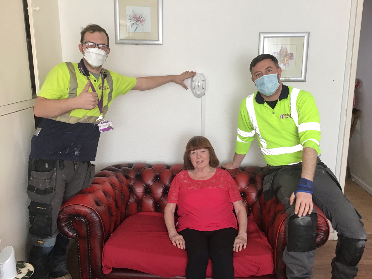 Mrs Kirby in her home with two halton housing operatives alongside the specialist alarm